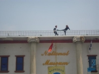 A police officer and a ninja fighting on the roof.